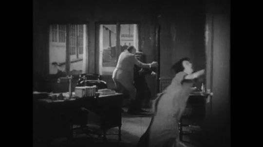 1920s: men and woman hide inside bathroom. lion smashes through transom. paw breaks door and swats at men as woman fights with feather duster.