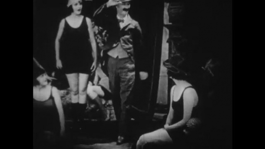 1920s:  man enters movie set with women in swimsuits. man in fur coat hooks pickaxe around man