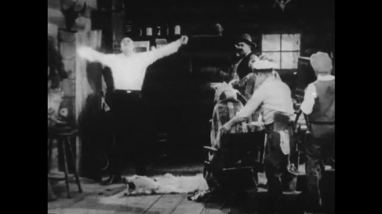 1920s: man points around room at men and sits next to movie camera. cowboy points whip and grabs woman wrapped in rug with feather hat and flapper dress. man with fur hate opens door and drops coat.
