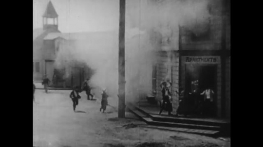 1920s: smoke pours out of buildings on street. horses pull fire engine as men in cars film chase. water sprays and rises on tied man in basement movie set as men crank camera.