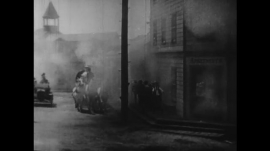 1920s: smoke pours from buildings as horse drawn fire engine stop. men get camera off car as man sends woman with babydoll into burning office. water floods basement set as man dives toward spray.