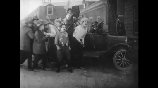 1920s: cowboy carries gas tank near camera car. men flee as man refuses to stop film. barrel explodes, destroys car and man crawls from wreckage.