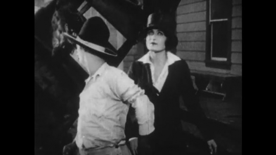 1920s: cowboy and woman stand on street. man cranks smoking camera with director in car wreckage. police race down street and jump on police car.