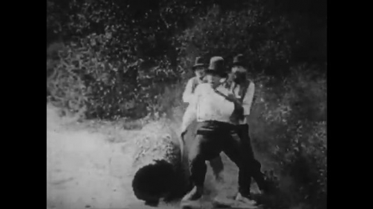 1920s: men pick up log and get hit by car. smoke clears with small wood in men