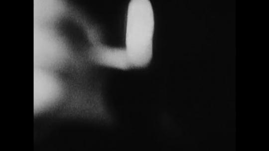 1960s: Close up, hand lights pipe, tilt down hookah. People smoke hookah.