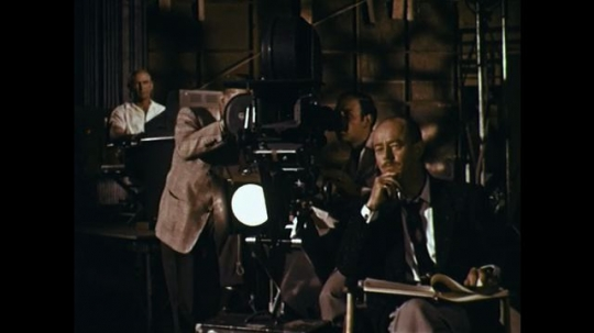 1960s:  cinematographer looks into movie camera as man with script sits nearby. man in suit talks with his hands. man talks and writes on small desk.