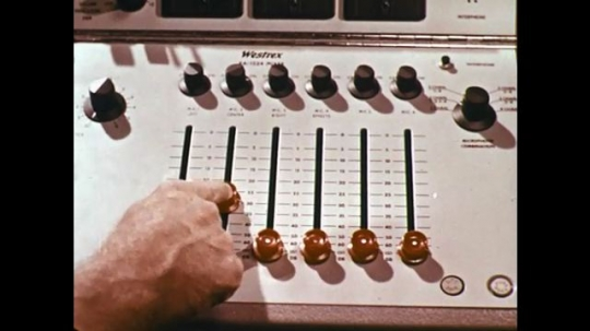 1960s: hand slides knobs on audio mixing board. men talk near machine and  giant ear photo. man talks next to storyboard drawings.