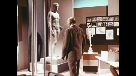 1960s: man walks past statue of naked man into office with storyboards. pencil points at drawings of how an ear hears sound waves.