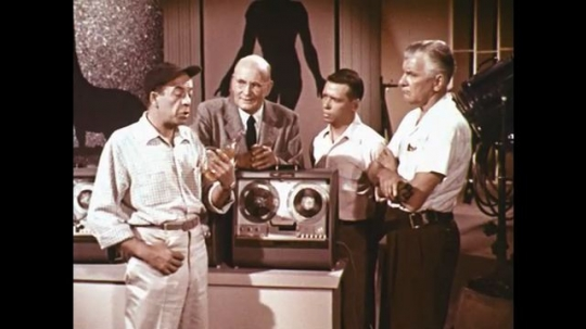 1960s: men talk about soda bottle while next to reel to reel tape recorders on movie set in soundstage.