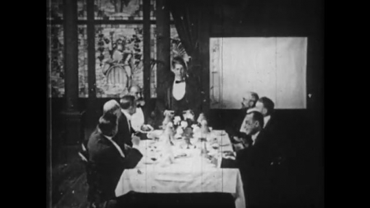 1910s: Men around dinner table, man stands, draws on paper.