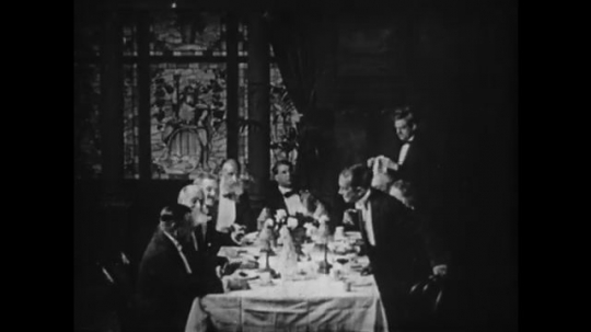 1910s: Man around dinner table, man stands. Intertitle. Men stand and toast.