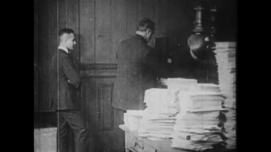 1910s: Men in office. Boy enters room, men pile stacks of paper in boy