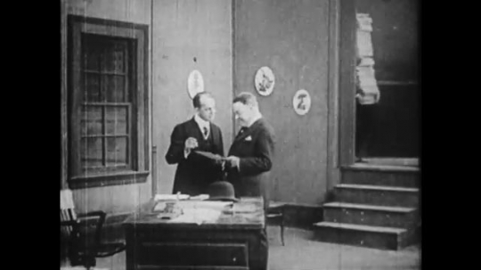 1910s: Men in office, boy enters with tall stack of papers, drops papers.
