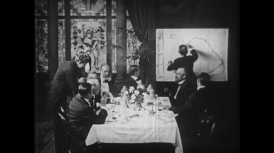 1910s: Men around dinner table, man drawing in background.