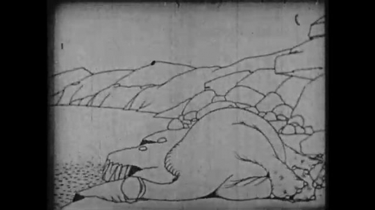 1910s: Animation, dinosaur laying on ground, scratches head with tail.
