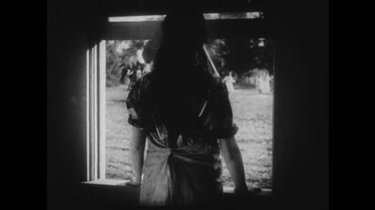 1910s: Young girl gazes out of window at other girls playing outside. Adult woman scolds young girl and they both begin cleaning the room they are in.