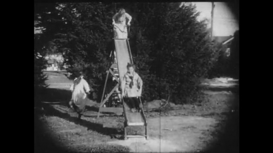 1910s: Girls play on a slide, another girl attempts to joint the fun but the group rejects her. A girl on a bench gets up and leaves her dolls behind.