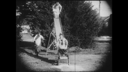 1910s: Group of girls play on a slide, another girl approaches a bench where some dolls have been left behind. She contemplates picking one up and eventually does.