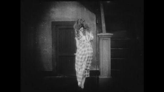 1910s: Young girl runs to a closet underneath some stairs, pulls a doll out from under her dress, then hides in the closet with the doll. In another shot, a different girl approaches a bench.