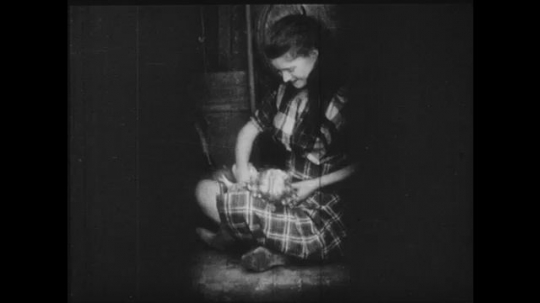 1910s: Girl sits in cramped space playing with a doll.