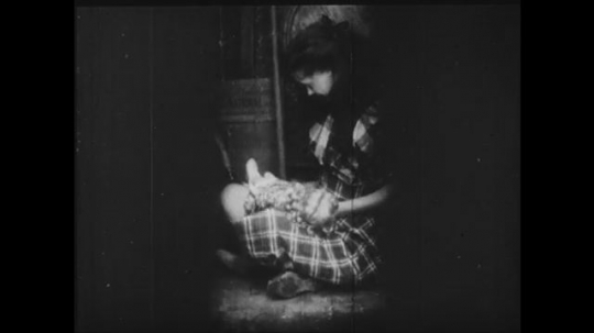 1910s: Girl sits in cramped space playing with a doll and accidentally breaks it. Another girl stands outside frantically looking around. A line of girls walk into a building.