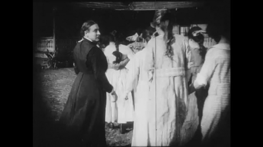 1910s: Girl rushes over to an adult woman and speaks to her, they both approach a line of girls and question them. Another girl sneaks out of a closet under a stairwell.