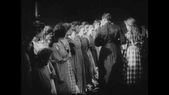 1910s: Adult woman and young girl walk down lineup of girls while questioning them. Another girl joins the lineup at the end with a look of apprehension. Man tears off piece of canvas from board.