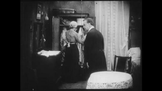 1910s: Woman opens wardrobe then clutches a piece of clothing while looking wistful, her husband comforts her. Different scene, a woman rushes in while yelling at a man. They go outside to feed cat.