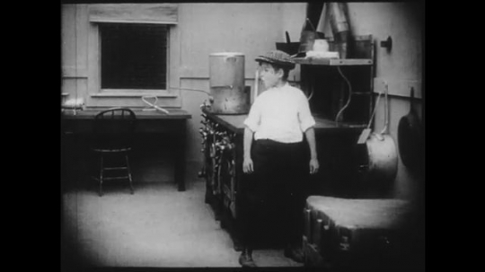 1910s: Young boy pulls an object out of a box hanging on a kitchen wall, then puts it in his pocket. Girl has her hand looked at while talking to an adult woman sitting in a chair in the same kitchen.