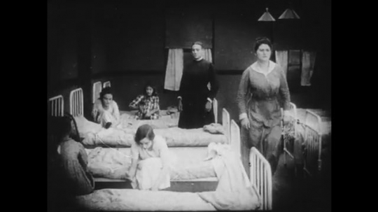 1910s: Schoolgirls getting into their beds. Teacher enters kitchen where one girl and an adult woman/housekeeper are talking, the girl is scolded by the teacher. Two schoolboys talk in their beds.