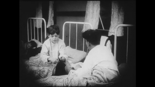 1910s: Schoolgirls and schoolboys get into their respective beds. The two boys talk to each other excitedly before going to sleep. One girl is threatened by the teacher.