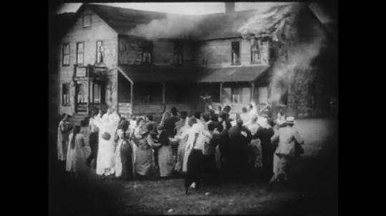 1910s: Large crowd panics outside of a burning building. People try to revive unconscious girl who was rescued from inside.