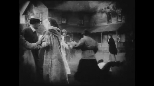 1910s: Large crowd panics outside of a burning building. People try to revive unconscious girl who was rescued from inside. Woman attempts to comfort another girl who looks concerned.