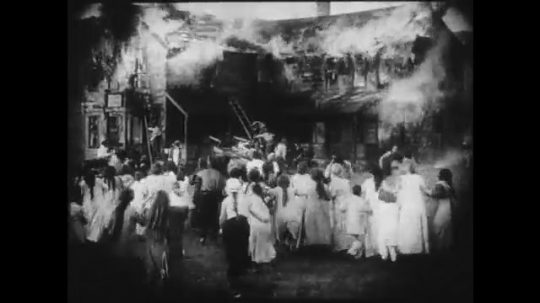 1910s: Large crowd panics outside of a burning building. A smaller group gazes at the destruction, some of them talk to a girl and a young man stares at her. Firefighters try to put out the flames.