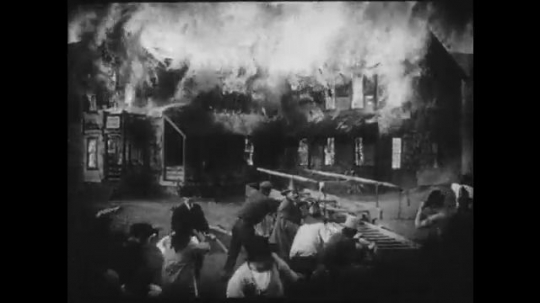 1910s: A building burns while firefighters flee from the scene. An elderly woman tucks a young girl into bed.