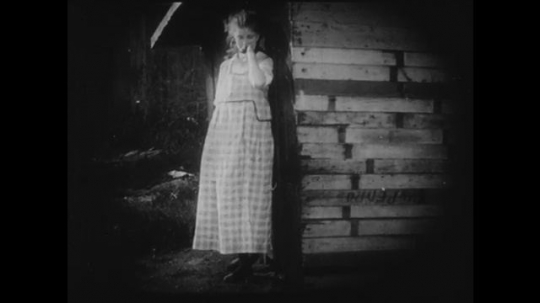 1910s: Young girl cries next to a shed. A group of adults and two young adults meet in a parlor. The two young adults are left alone and laugh together.