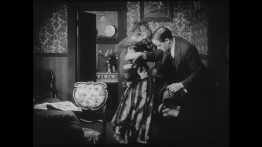 1910s: Young man inspects young woman
