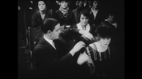 1910s: Young couple watch a movie in a theater, the girl removes her jacket. The movie is a Western.
