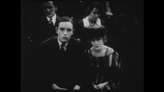 1910s: Young couple watches a movie in a theater, they start to hold hands nervously.