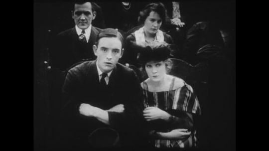 1910s: Young couple watches a movie in a theater, they watch the screen with apprehension. Movie shows man dying after being shot and woman fetching water from well.