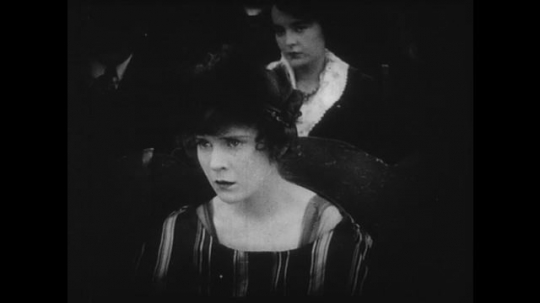1910s: Young couple watches a movie in a theater, they watch the screen with apprehension. Movie shows woman realizing that her lover has been shot.