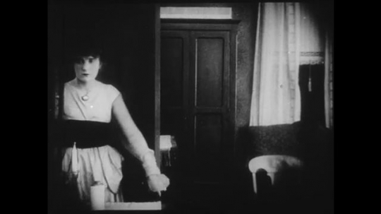 1910s: Young woman enters a parlor and overhears people outside concerned that they heard a gunshot, she looks guilty/worried. Woman walks around in living room.