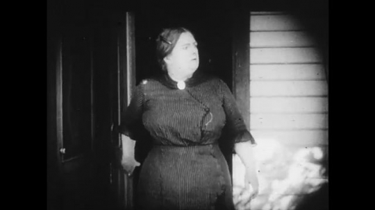 1910s: Woman walks outside calling for young woman. Young woman leaves parlor and goes outside to talk with older woman.