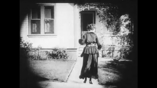 1910s: Young woman sneaks into a house and looks shocked by what she sees.