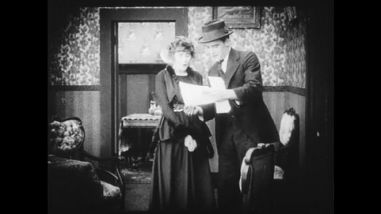 1910s: Man shows woman some papers and then they talk excitedly.