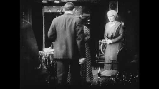1910s: Two men and two women speak in a parlor, then the men leave. A young woman nods off in a chair in another room.