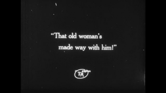 1910s: Text slides. Shots of men talking on stairs then approaching a third man. Young woman looks and walks around a room.