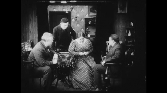 1910s: A group of men question two women at a house. A young woman approaches the house.