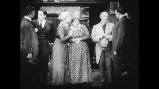 1910s: A large group of men in a house, a woman pleads with one of them. A young woman outside eavesdrops and looks guilty.