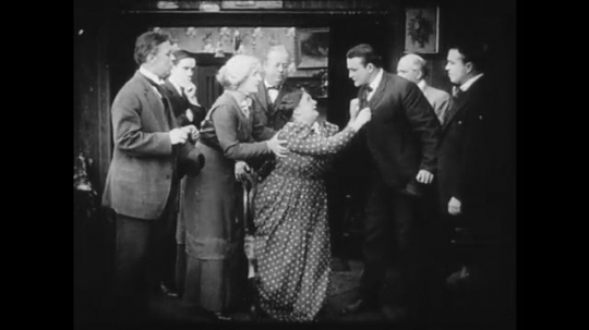 1910s: A large group of men in a house, a woman pleads with one of them. A young woman enters the house and confesses to the crime.
